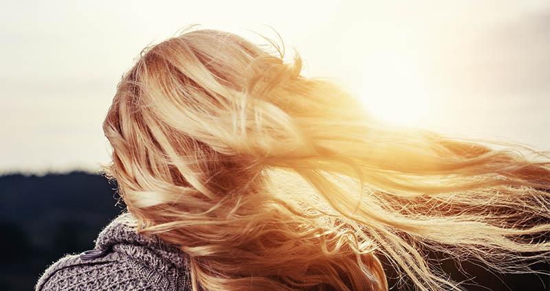 Mujer rubia usando champú desamarillador en cabello con luces