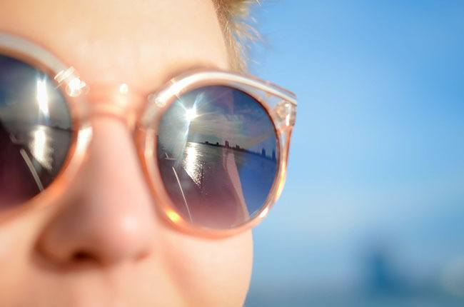 Chica con Antiarrugas y Gafas de sol mirando al mar