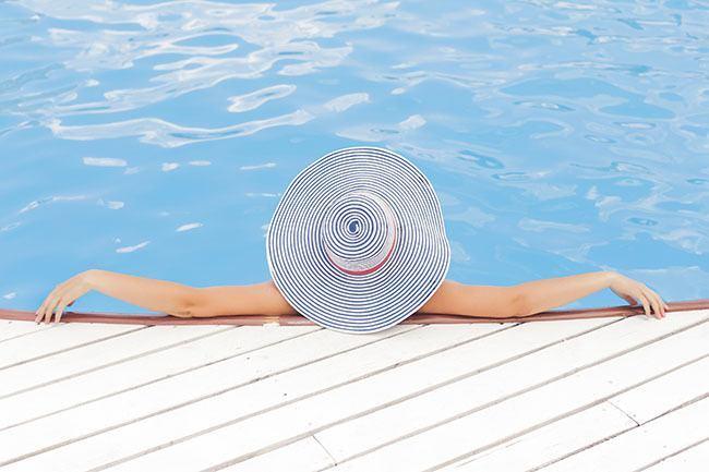 Mujer tumbada en piscina hidratándose