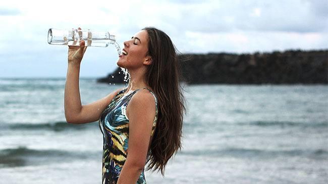 Mujer hidratando su piel al lado del mar