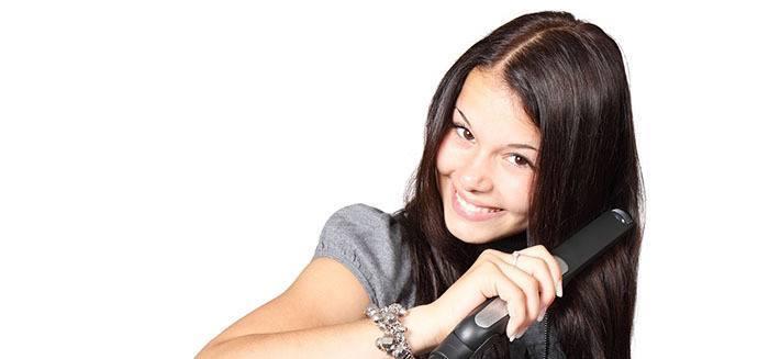 Chica se plancha el pelo para aumentar tiempo de tratamiento con keratina