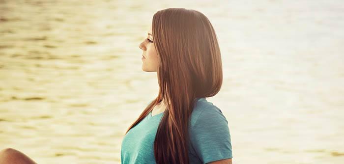 Chica mirando lago con pelo cauterización capilar keratina