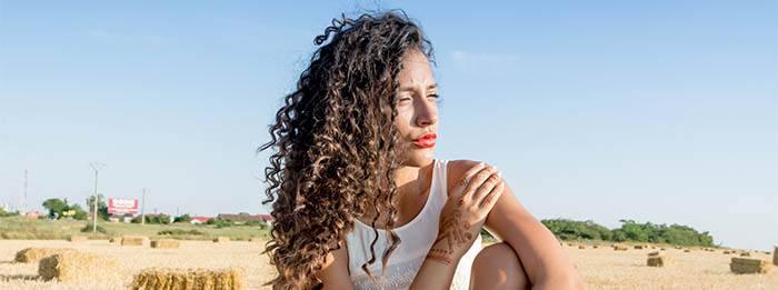 Chica pelo muy rizado de cara al sol